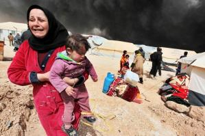 Syrian woman rushes her child from danger.