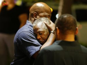 A Charleston community member comforts a man mourning news learned of nine Emanuel African Methodist Episcopal church members shot and killed during bible study on Wednesday night, June 17, 2015 in Charleston, S.C. Photo courtesy: Associated Press